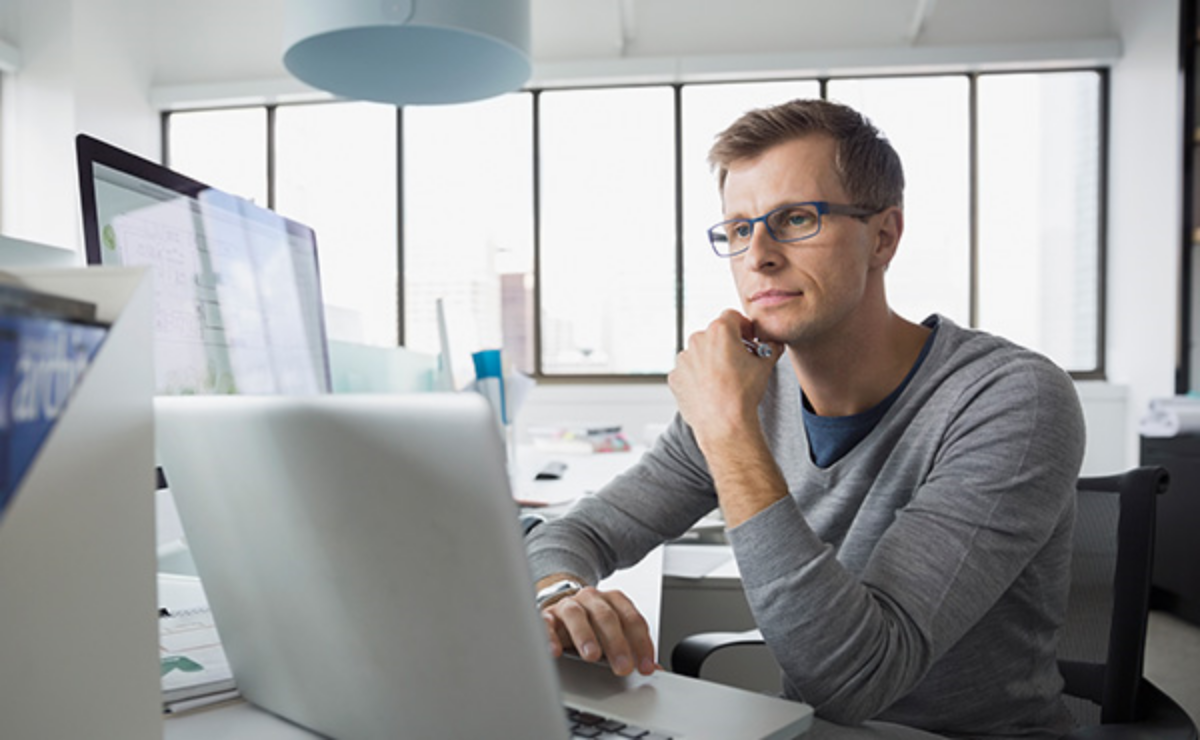 Man at desk working on laptop in office